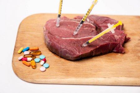 Photo pour Seringues dans de la viande crue et des pilules hormonales sur planche à découper isolée sur blanc - image libre de droit