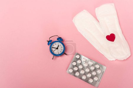 Top view of feminine pads with paper heart, birth control pills and alarm clock on pink background