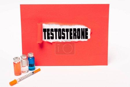Photo pour Lettrage de testostérone dans un trou de papier rouge, seringue et bocaux de médicaments hormonaux sur fond blanc - image libre de droit