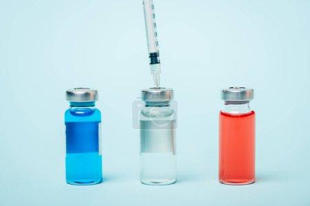 Photo pour Vue de près de la seringue et des bocaux de médicaments hormonaux sur la surface bleue - image libre de droit