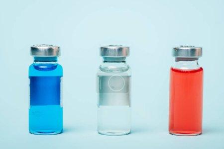 Photo pour Vue en gros plan de pots colorés avec des médicaments hormonaux sur une surface bleue - image libre de droit