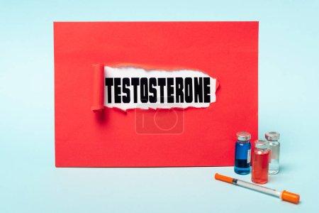 Photo pour Bocaux avec médicaments hormonaux et seringue près de la testostérone lettrage dans un trou de papier rouge sur fond bleu - image libre de droit