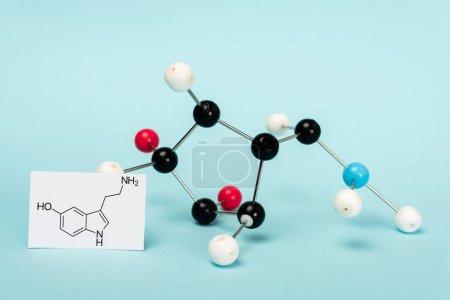 Photo pour Formule moléculaire de sérotonine sur carte près de la construction hormonale sur fond bleu - image libre de droit