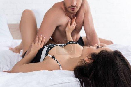 Photo pour Concentration sélective de la femme attrayante touchant petit ami et couché sur le lit dans la chambre - image libre de droit
