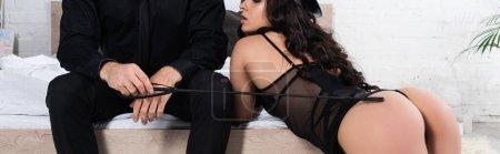 Photo pour Vue croustillante d'une policière sur les quatre près du lit et d'un homme touchant les fesses d'une femme avec un fouet de fouet dans la chambre, photo panoramique - image libre de droit