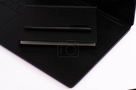 Photo pour Notebook noir et stylo sur clavier d'ordinateur portable isolé sur blanc - image libre de droit