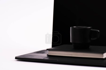 Photo for Black notebook and cup on laptop with blank screen isolated on white - Royalty Free Image
