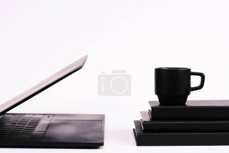 Photo for Cup on notebooks near black laptop on white - Royalty Free Image