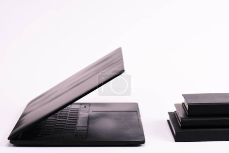 Photo for Notebooks near black and modern laptop on white - Royalty Free Image