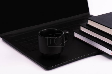 Photo for Notebooks and cup near black and modern laptop isolated on white - Royalty Free Image