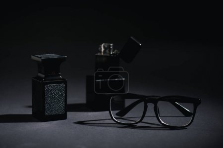 Photo for Selective focus of glasses and perfume bottle near lighter on black - Royalty Free Image