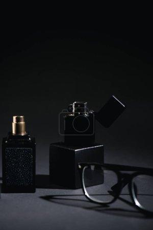 Photo pour Foyer sélectif de briquet près de verres et bouteille de parfum sur noir - image libre de droit