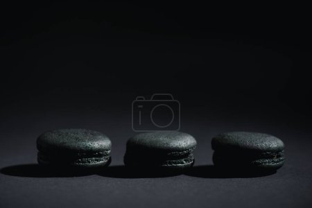 Photo for Prepared dark macarons on black with copy space - Royalty Free Image