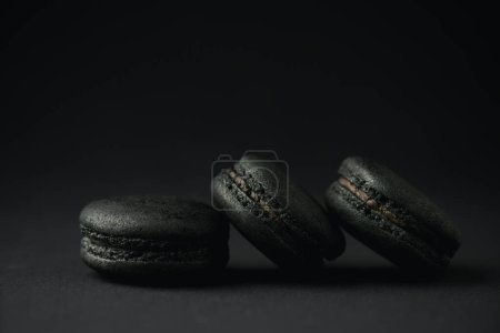 Photo for Dark and tasty macarons on black with copy space - Royalty Free Image