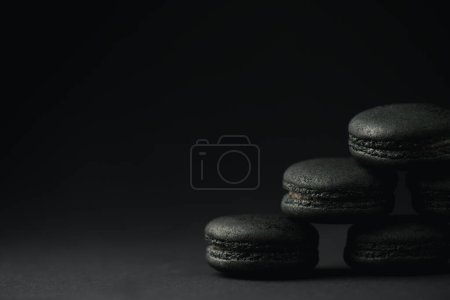 Photo pour Macarons sombres et doux sur noir avec espace de copie - image libre de droit