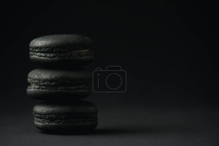 Photo for Delicious and dark macarons on black with copy space - Royalty Free Image