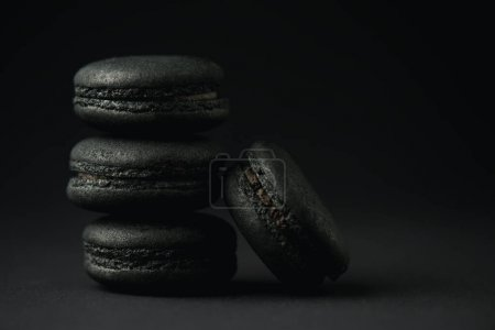 Photo for Tasty and dark macarons on black with copy space - Royalty Free Image