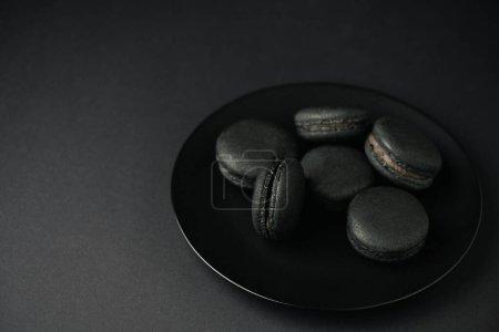 Photo pour Assiette avec des macarons savoureux et sombres isolés sur noir - image libre de droit