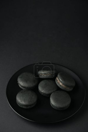 Photo for Top view of plate with dark and tasty macarons on black - Royalty Free Image