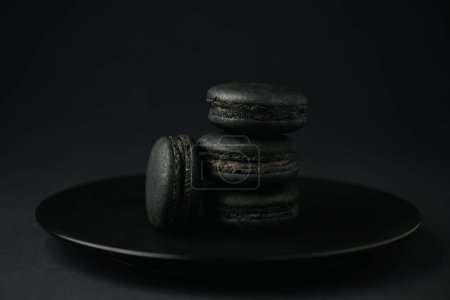 Photo pour Plaque avec macarons foncés sur noir avec espace de copie - image libre de droit