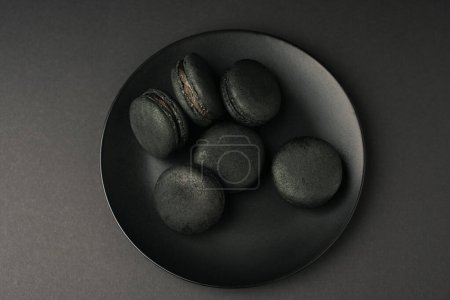 Photo for Top view of plate with dark macarons isolated on black - Royalty Free Image