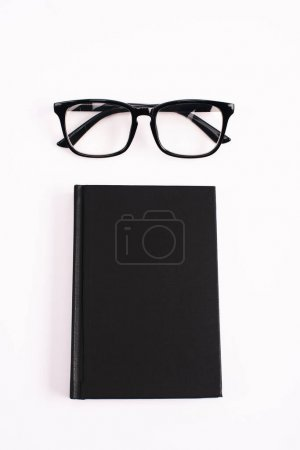 Photo for Top view of glasses and black notebook isolated on white - Royalty Free Image