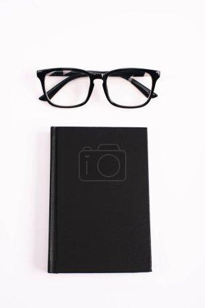 Photo pour Vue du dessus des lunettes et carnet noir isolé sur blanc - image libre de droit