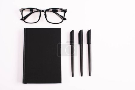 Photo for Flat lay with pens near glasses and black notebook isolated on white - Royalty Free Image