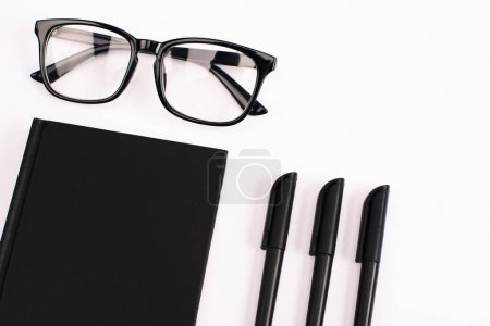 Photo for Top view of pens near glasses and black notebook isolated on white - Royalty Free Image