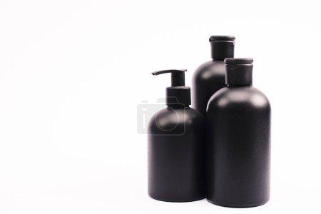 botellas negras con loción corporal aislada en blanco