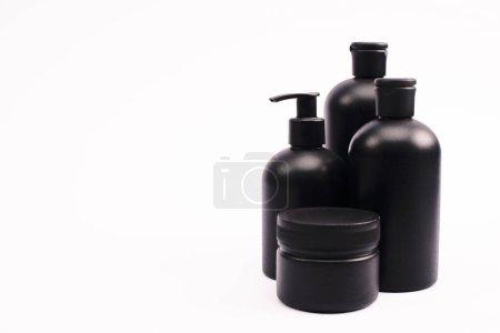 envase negro cerca de botellas con loción corporal aislada en blanco