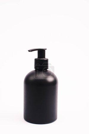 Photo pour Bouteille noire avec lotion pour le corps isolée sur - image libre de droit