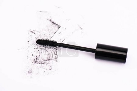 Photo pour Top view of smudged mascara near mascara brush on white - image libre de droit