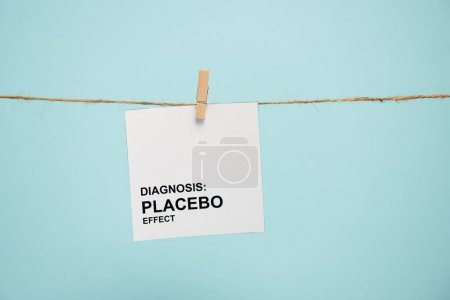 Card with diagnosis placebo effect lettering on rope with pin isolated on blue