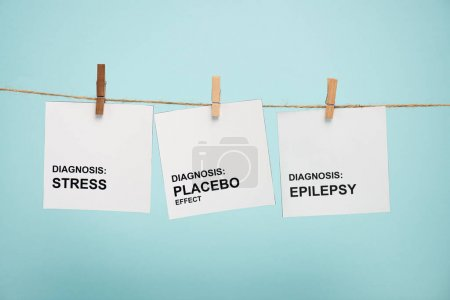 Photo for Cards with stress, placebo effect and epilepsy diagnoses lettering on rope with pins isolated on blue - Royalty Free Image