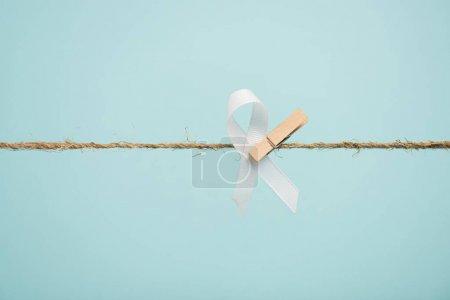 Photo pour Ruban blanc avec épingle sur corde isolé sur bleu - image libre de droit