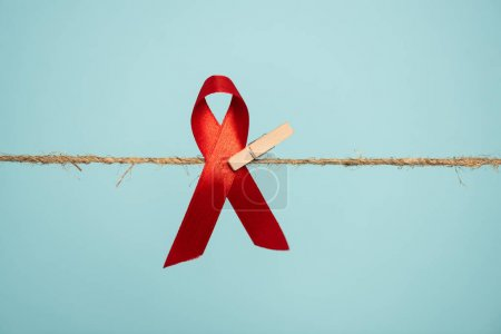 Photo pour Épinglette avec aide sensibilisation ruban rouge sur corde isolé sur bleu - image libre de droit