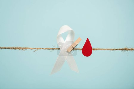 Photo for White ribbon with pin and paper in blood drop shape on rope isolated on blue, hemophilia concept - Royalty Free Image