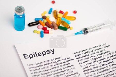 Photo pour Papier avec inscription épileptique près du pot de vaccin, seringue et pilules sur fond blanc - image libre de droit