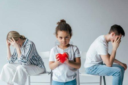 Photo pour Orientation sélective d'un enfant africain américain adopté tenant le cœur rouge près de parents adoptifs divorcés sur le gris - image libre de droit