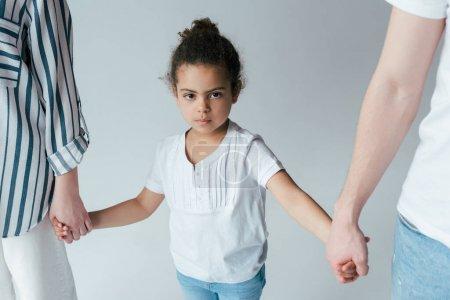 Photo pour Adopté enfant afro-américain tenant la main avec des parents divorcés isolés sur gris - image libre de droit