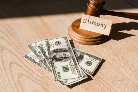 Photo pour Marteau près des billets en dollars et du papier avec inscription sur le bureau - image libre de droit