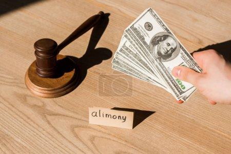 Photo pour Vue recadrée de l'homme tenant des billets en dollars près du marteau et du papier avec inscription sur le bureau des pensions alimentaires - image libre de droit