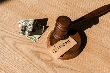 Photo pour Vue du haut du marteau en bois près du billet en dollar et du papier avec inscription sur le bureau - image libre de droit