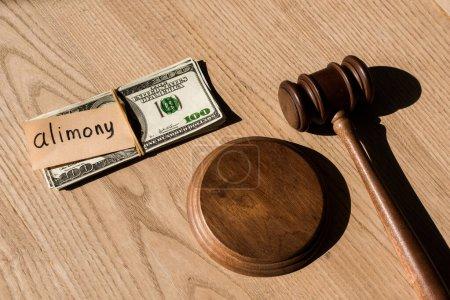 Photo pour Vue du haut du marteau près des billets en dollars et du papier avec lettrage de pension alimentaire sur un bureau en bois - image libre de droit