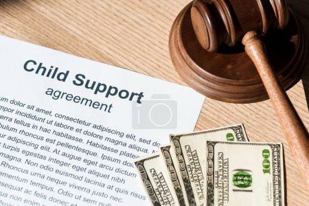 Photo pour Marteau en bois près du document avec accord de pension alimentaire pour enfants et billets en dollars - image libre de droit