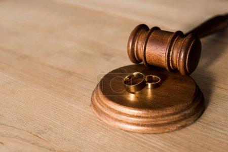 Photo pour Focalisation sélective du marteau et des bagues de fiançailles sur le bureau - image libre de droit