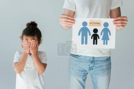 père tenant du papier avec la famille dessinée et lettrage pension alimentaire près bouleversé afro-américaine fille isolée sur blanc