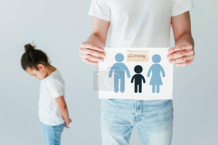 foyer sélectif du père tenant le papier avec la famille dessinée et le lettrage de pension alimentaire près bouleversé fille afro-américaine isolée sur blanc