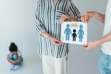 selective focus of parents holding paper with drawn family and alimony lettering near upset african american daughter on white